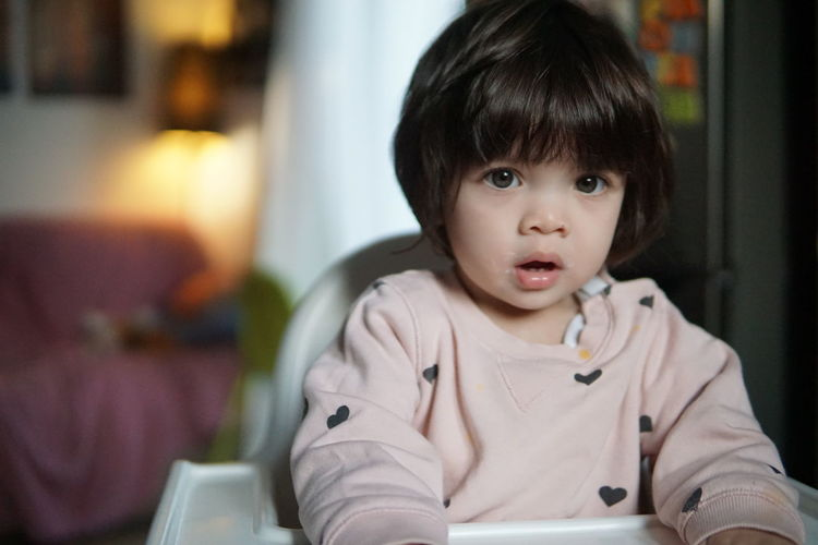 Portrait of cute baby girl sitting on high chair at home