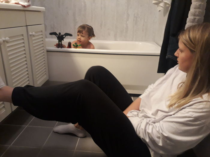 Woman Looking At Boy Playing With Toys In Bathtub At Home
