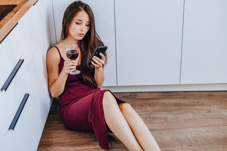 Young woman using mobile phone while sitting on wall