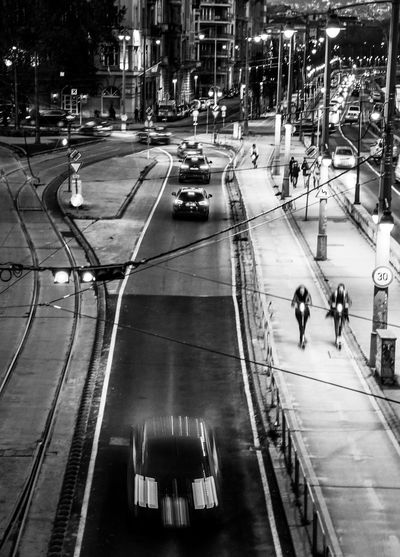 High angle view of people walking on city street at night