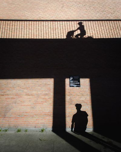 Silhouette man standing by brick wall