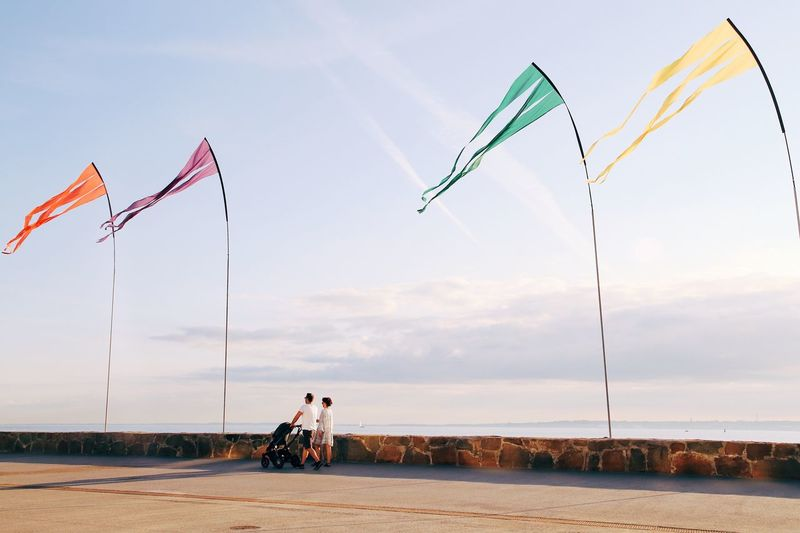 Seaside Blue Sky Wallpaper Unrecognizable People Family Summer Vibes Flags In The Wind  Coastal Open Space Flags Sidewalk Coastal Walk Full Frame Sky Real People Nature Transportation Water Leisure Activity Mode Of Transportation Lifestyles Flag People Togetherness Day Beach Sea Outdoors
