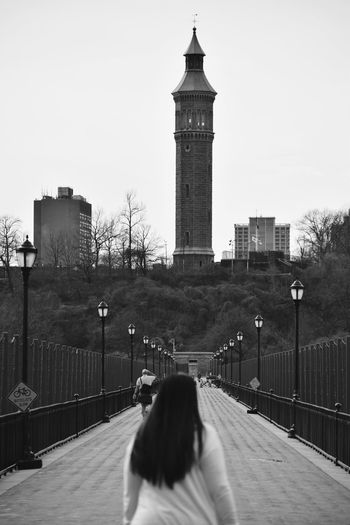 Rear view of people walking on high bridge with water tower in background