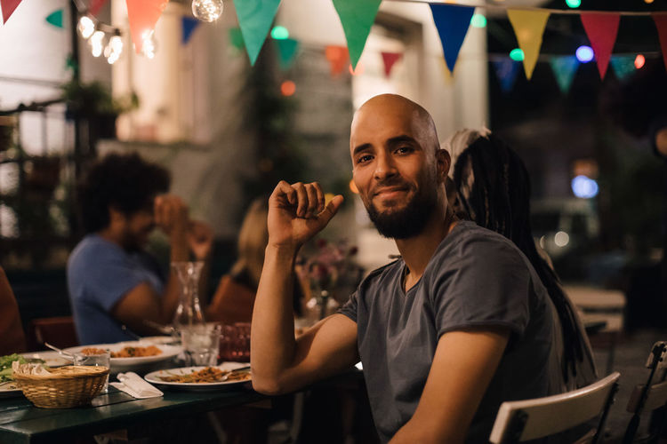 Portrait of smiling young man with shaved head sitting at table during dinner party in backyard