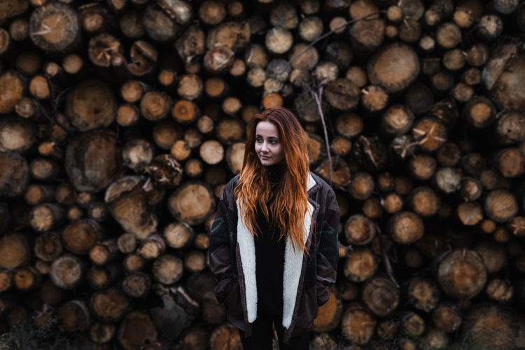Full length of young woman standing on log
