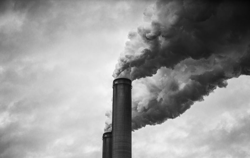 smokestacks pouring smoke into the atmosphere Air Pollution Chimney Day Emitting Factory Industry Low Angle View No People Outdoors Sky Smoke - Physical Structure Smoke Stack