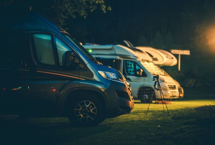 Travel Industry. Modern Camper Vans in the RV Park During Night Hours. Rving Theme. Rving Camper Van Motorhome Motorcoach Rv Park Land Vehicle Transportation Motor Vehicle Mode Of Transportation Nature Outdoors Camping Campsite Car Parking Night
