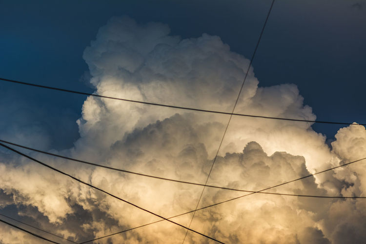 Framed by the city. Cable Cloud - Sky Electricity  No People Outdoors Power Line  Sky Sunset