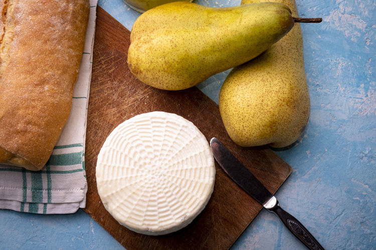 Fresh cow cheese with pears Food Food And Drink Freshness Healthy Eating Fruit Wellbeing Indoors  High Angle View No People Still Life Table Pear Wood - Material Directly Above Close-up Group Of Objects Dish Towel Cutting Board Medium Group Of Objects Studio Shot Ripe Table Knife Cheese Pears Bread Knife