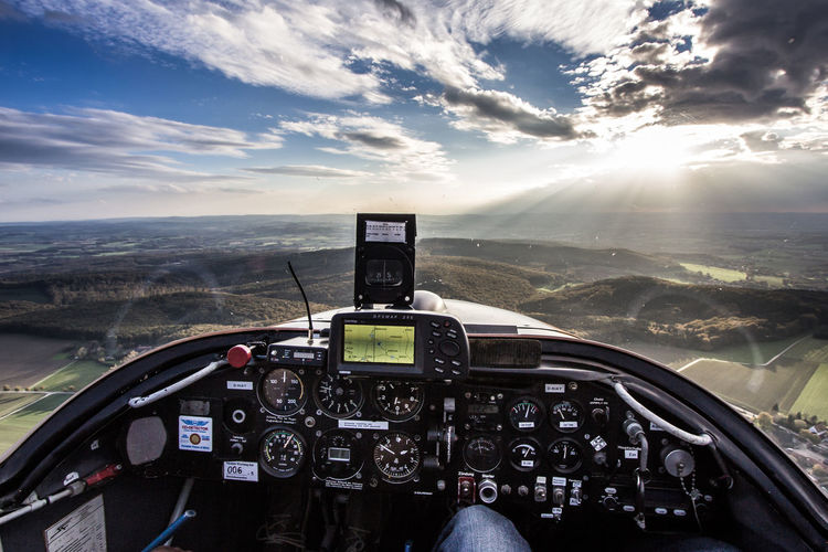 Midsection Of Pilot Flying Airplane Over Mountains