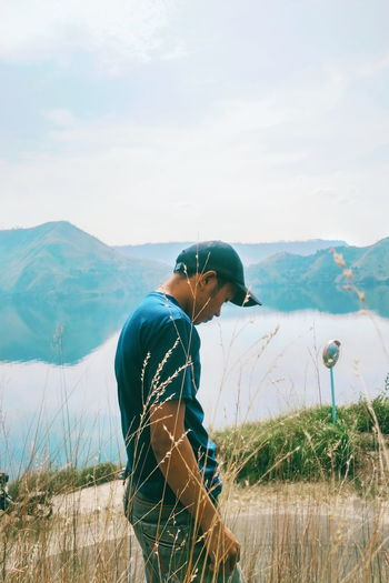 Young man on mountain against sky