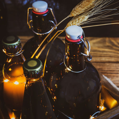 Bottles with cold, homemade, light and dark, unfiltered beer with ears of wheat and twinkling lights