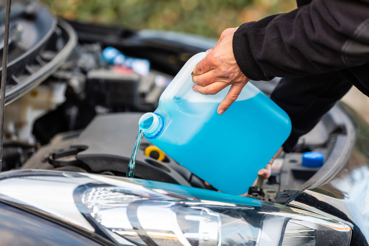 Cropped hands of mechanic pouring blue liquid in car engine