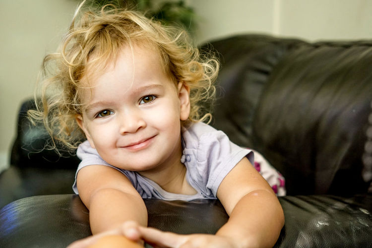 Portrait of smiling girl relaxing on sofa at home