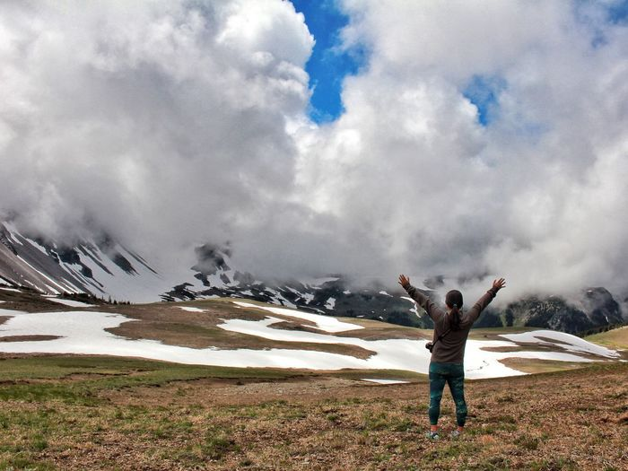 Rear View Of Hiker Standing With Arms Raised Against Clouds Covering Mountains