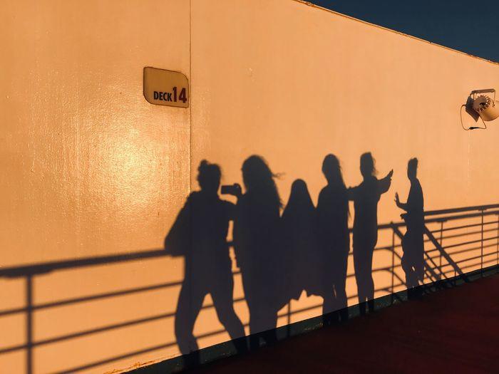 Silhouette people standing against orange wall