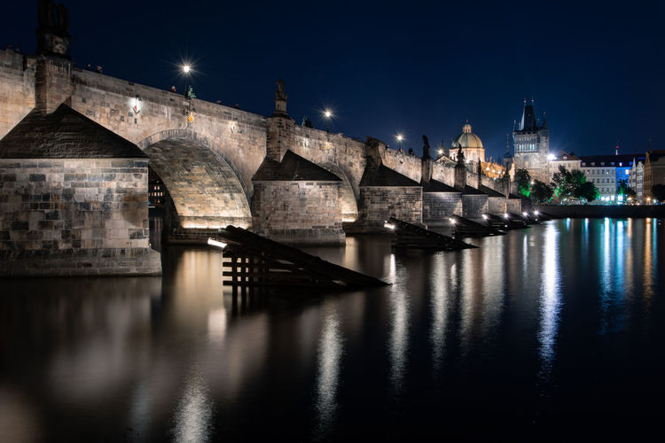 View of charles bridge over river at night