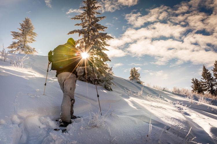 Man hiking on snowy mountain against sky