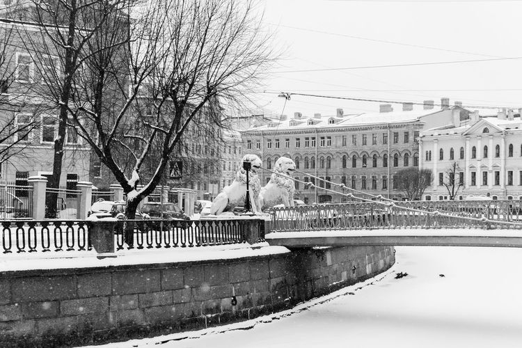 Bridge over canal amidst buildings against sky during winter