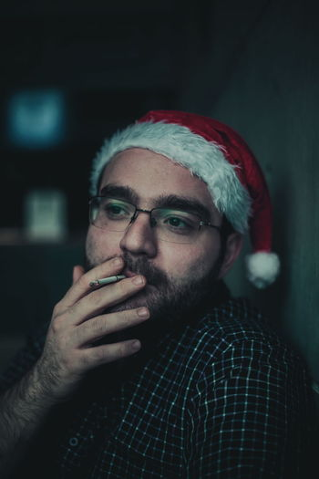 Thoughtful young man smoking cigarette while wearing santa hat at home
