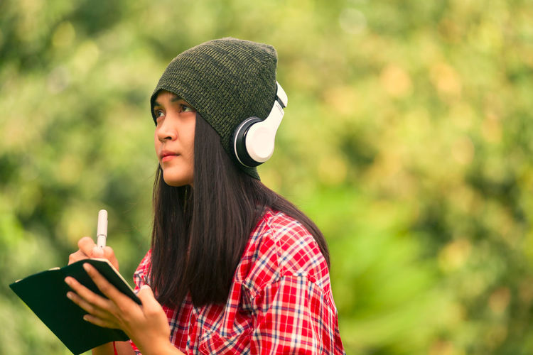 Young Woman Wearing Headphones While Writing In Book Outdoors