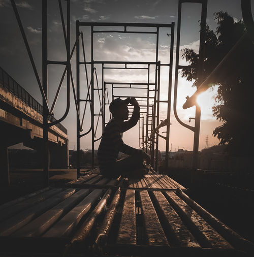 Side view of silhouette woman sitting on road against sky