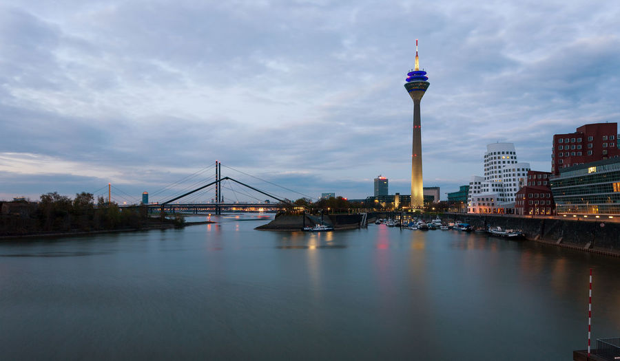 Rhine tower in Dusseldorf, Germany. Germany Düsseldorf Düsseldorf, Medienhafen City Rhine Tower Media Harbour Rhine Architecture Built Structure Building Exterior Water Sky Tower Cloud - Sky Travel Building Tall - High Travel Destinations Waterfront Bridge River Bridge - Man Made Structure Transportation Office Building Exterior No People Skyscraper Outdoors Spire  Modern Cityscape Bay