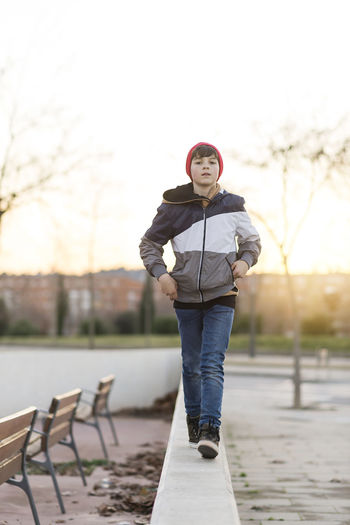 Young teenager portrait wearing a red hat Casual Clothing Day Focus On Foreground Front View Full Length Leisure Activity Lifestyles Looking At Camera One Person Outdoor Photography Outdoors Park Park - Man Made Space Portrait Real People Sky Standing Sunset Teen Teenager Walking Warm Clothing Young Adult Young Women