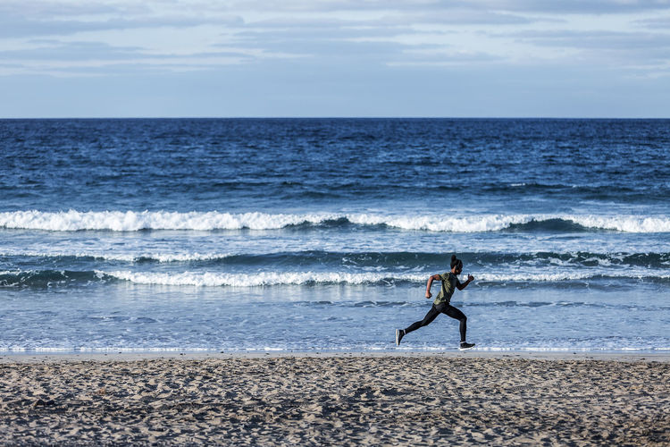 Anonymous black sportsman running near sea Sea Horizon Horizon Over Water Beach Land Sky Water Scenics - Nature Beauty In Nature Motion Nature Full Length Wave Tranquil Scene People Cloud - Sky Men Real People Day Outdoors Man Running Young Adult Sprinting African American