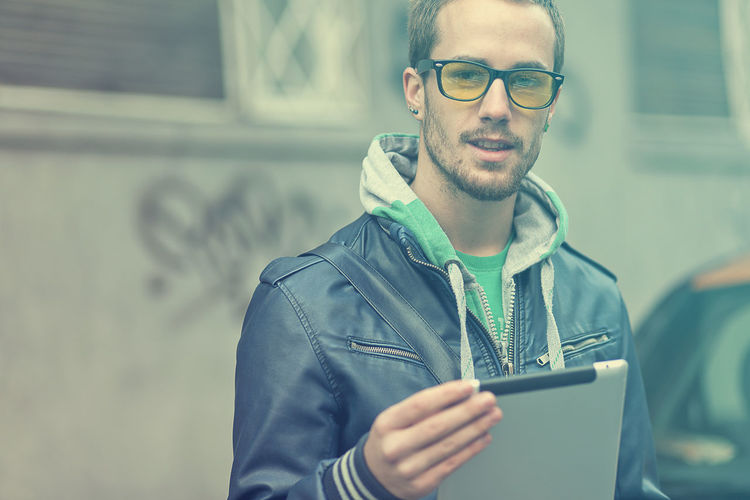 Portrait Of Young Man Using Digital Tablet While Standing On Street In City
