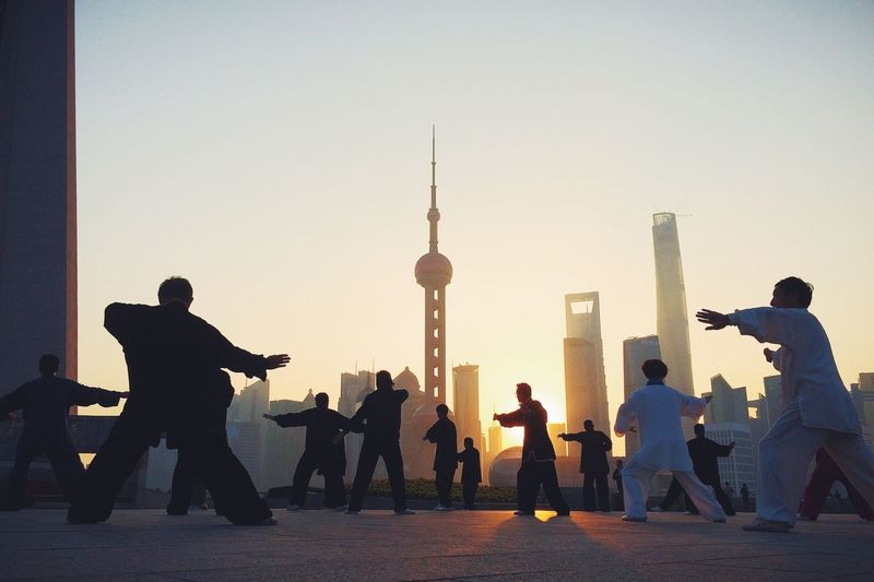 Men Performing Tai Chi Against Oriental Pearl Tower During Sunrise In City
