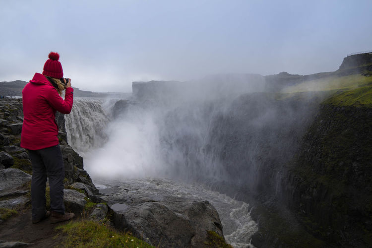 Woman photographing while standing by waterfall against sky