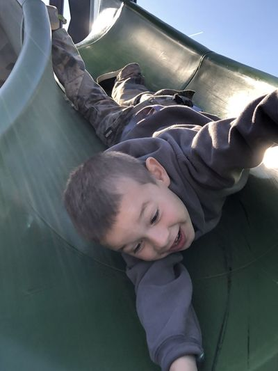 Cute boy playing on slide in playground