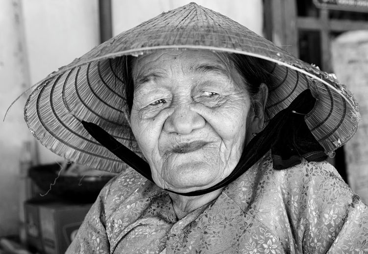 Woman wearing asian style conical hat while looking away at home
