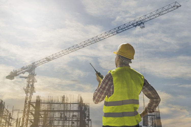 Rear View Of Male Worker Talking On Walkie-Talkie Against Incomplete Building