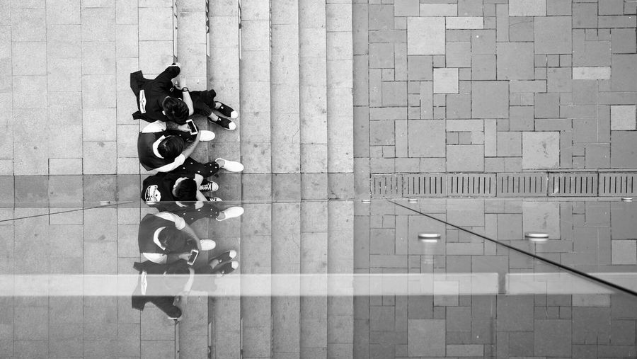 Directly above shot of friends sitting at staircase reflecting in glass