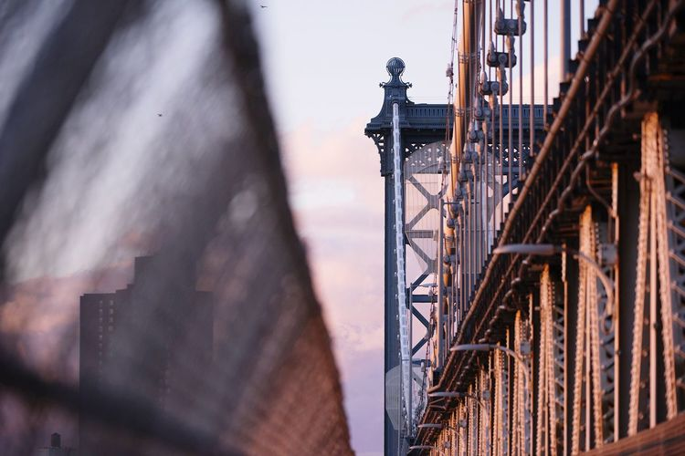 Manhattan Bridge at sunset connecting Manhattan to Brooklyn in New York City No People Outdoors Built Structure Day Low Angle View Architecture Travel New York New York City Illuminated Transportation Bridge - Man Made Structure River Travel Destinations Suspension Bridge Bridge