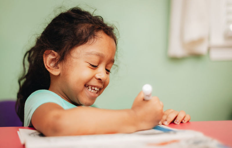 Portrait of cute girl smiling while sitting on table