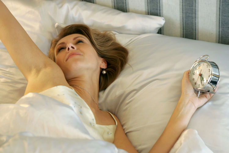 High Angle View Of Woman Lying On Bed At Home