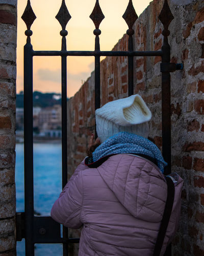 Rear view of woman standing by gate and wall in winter