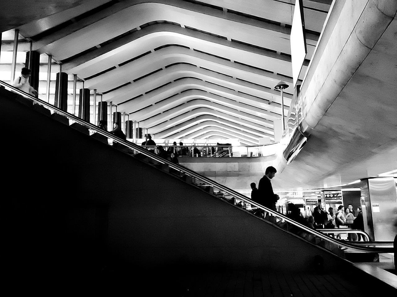 real people, indoors, large group of people, modern, men, lifestyles, escalator, architecture, transportation, women, staircase, leisure activity, built structure, steps and staircases, railroad station, public transportation, walking, convenience, illuminated, transportation building - type of building, the way forward, low angle view, day, technology, commuter, people, adult, adults only