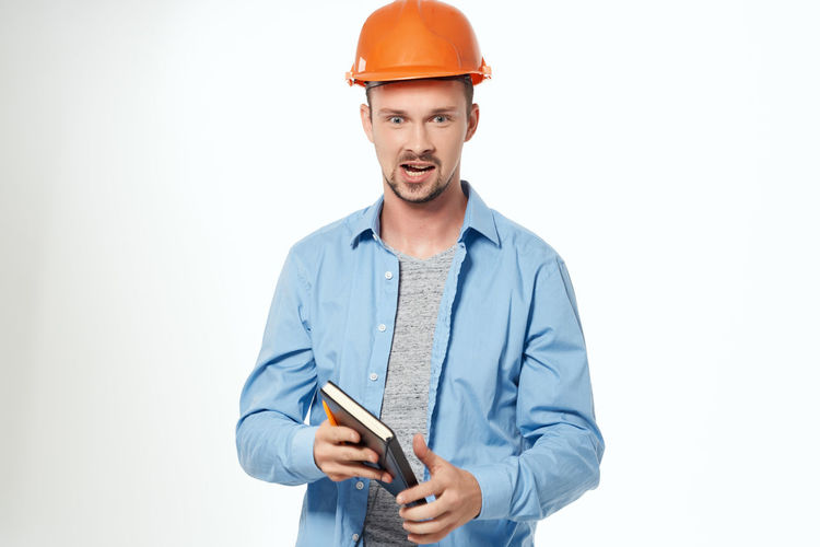 Young man using smart phone against white background