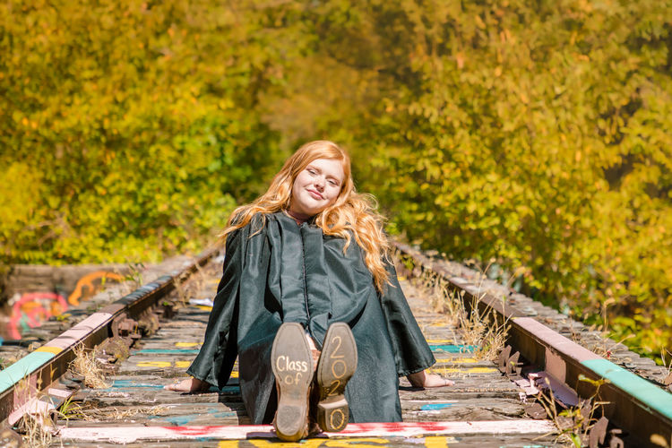 Portrait of teenage girl smiling while sitting on railroad track against trees