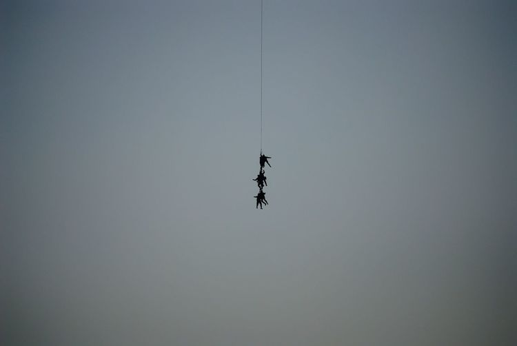 Low angle view of silhouette people hanging on rope against clear sky