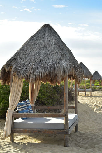 glamping beach bed relaxation on the shore Beach Life Bed Morning Light Absence Beach Beauty In Nature Built Structure Cloud - Sky Day Day Bed Glamping Hut Land Nature No People Outdoors Relaxation Roof Sand Sky Solitude Sunlight Thatched Roof Tranquil Scene Tranquility Umbrella