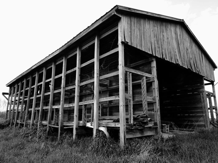 Low angle view of abandoned barn on field against sky