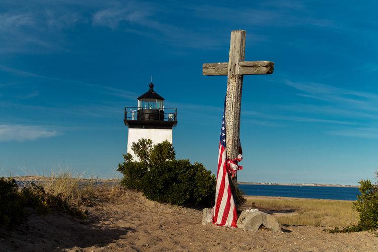 Cross by lighthouse on beach against blue sky