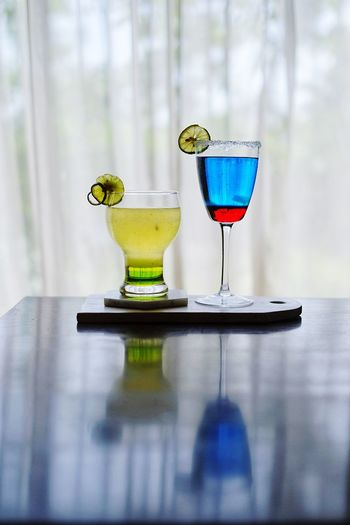 Drinks on table against window