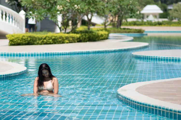 Smiling young woman sitting in swimming pool