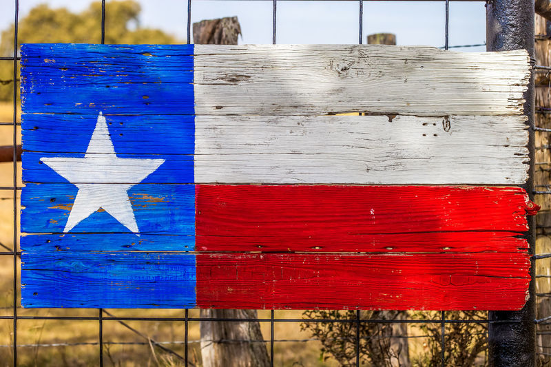 Texas flag painted on weathered wooden boards Country Farm Patriotic Ranch Republican Texas Texas Flag USA Wood Blue Boards Close-up Day Decoration Fence Lone Star State No People Outdoors Pride Red Red, White And Blue Spring Star Wood - Material